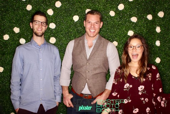 Photo booth with a fake hedge backdrop