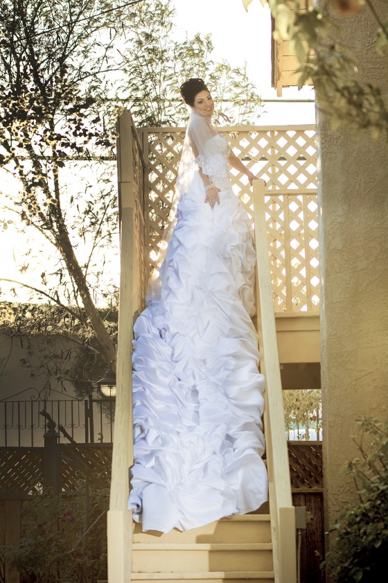 A beautiful bride and her long dress shine in the light