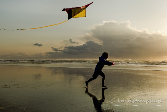 Flying a kite at the beach.