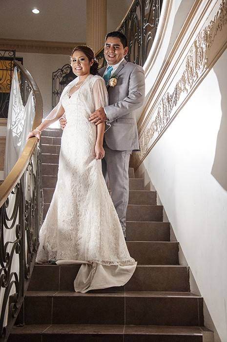Wedding Couple take their picture on mansion stairway.